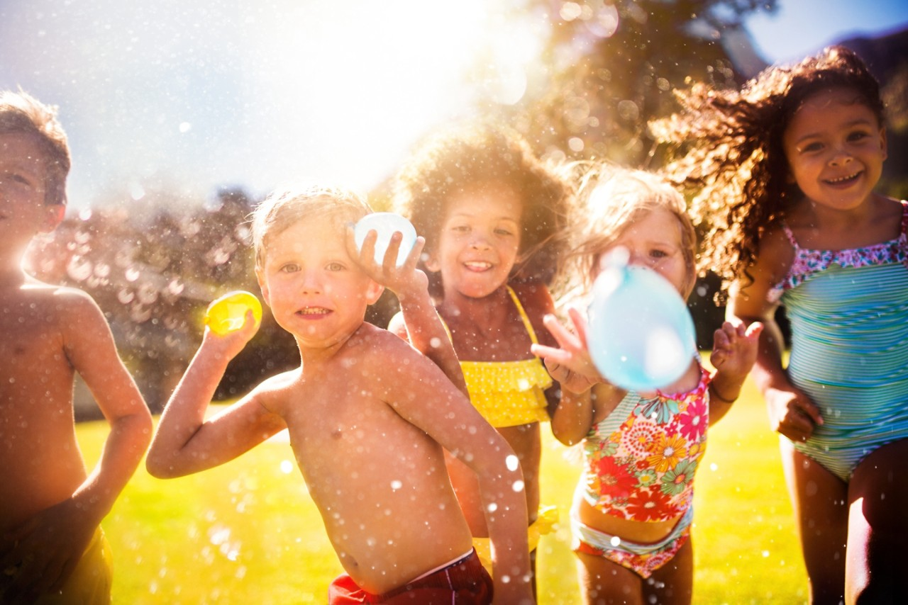 Happy mixed racial group of kids playfully throwing water balloons straight at the camera